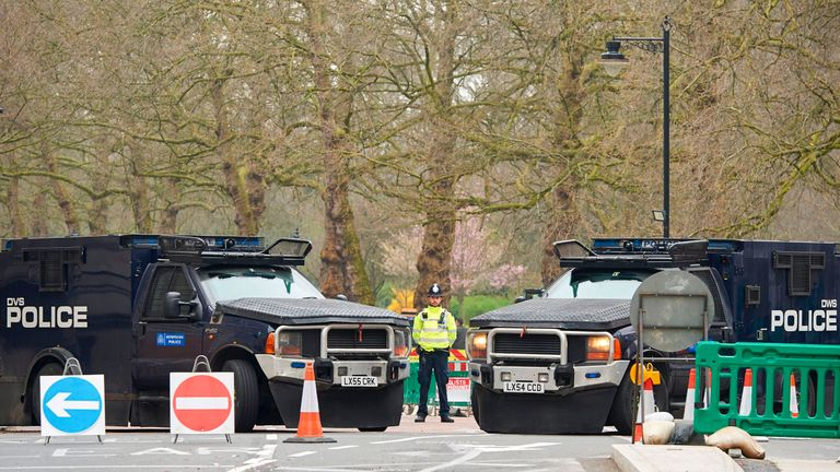 A police officer stands between armoured police personnel carriers on a street leading to the Houses of Parliament