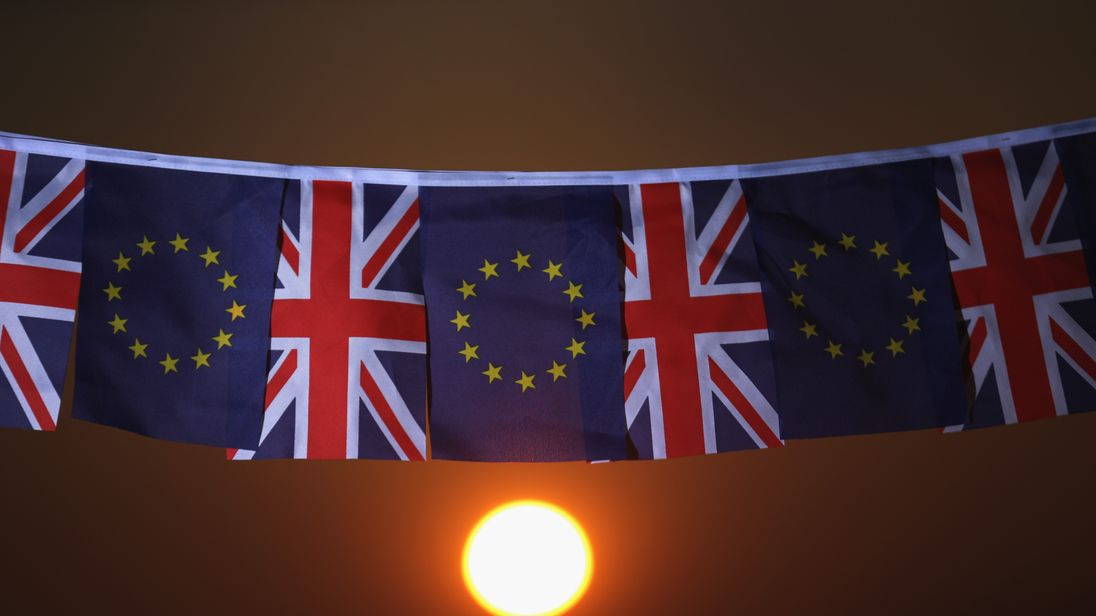 The EU and UK flags fly on a line at sunset