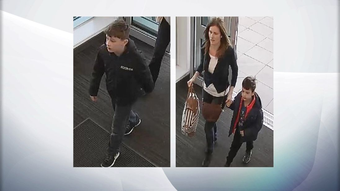 Police-issued CCTV images show Louis Madge (L) and his mother Samantha Baldwin holding hands with his brother Dylan