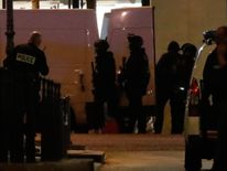 Police secure a side street as others conduct an investigation on the Champs Elysees Avenue