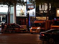 Firefighters and rescuers stand by the site of a shooting on the Champs Elysees in Paris