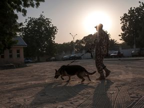 A Nigerian soldier with his sniffer dog patrols the Maiduguri State Specialist Hospital grounds on January 18, 2017