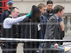 A man is led away by police in Westminster after an arrest was made on Whitehall