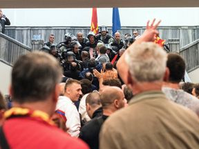 Police officers try to hold back protesters in Macedonia's parliament building