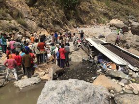 Indian rescue personnel and volunteers stand amidst wreckage and victims after a bus accident, at the bottom of a ravine near the River Tons