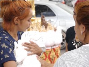 Chiranut Trairat cries as she holds her dead baby girl in her arms