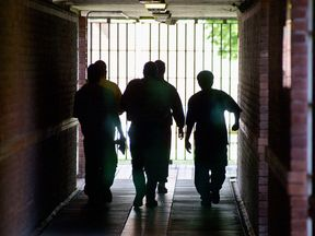 Inmates and guards walk along one of the corridors of HMP/YOI Feltham