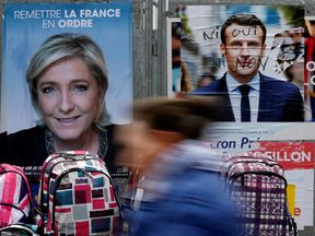 A woman walks past posters for Marine Le Pen and Emmanuel Macron in Bethune