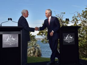 Mike Pence (L) and Malcolm Turnbull (R) shake hands on the shores of Sydney Harbour