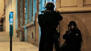Armed police officers block the access of a street near the Champs-Elysees
