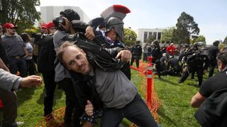 A protestor is pulled from a confrontation by a pro-Trump supporter