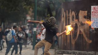 Demonstrators clash with riot police during a rally against Venezuela's President Nicolas Maduro in Caracas