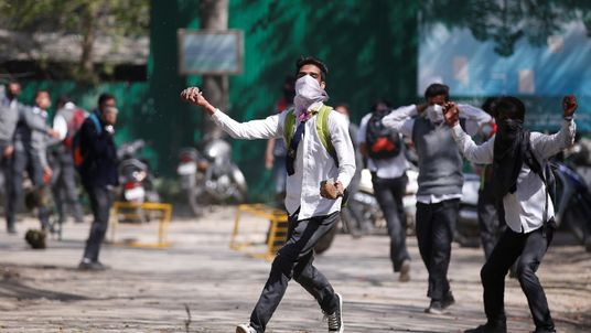 A Kashmiri student throws a piece of stone during a protest in Srinagar