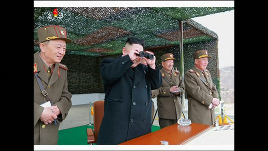 Kim Jong-Un smiles as he watches the action