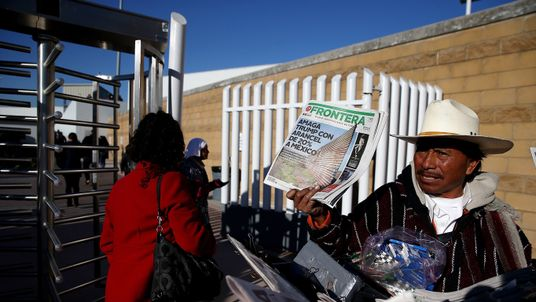 A Mexican vendor holds a newspaper with a front page story about Donald Trump's proposed tax on Mexico to pay for a border wall