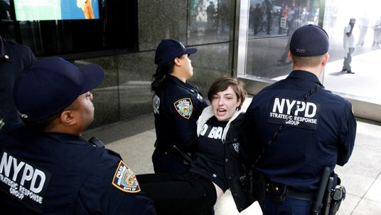 New York City Police officers (NYPD) carry a protestor after making arrests for demonstrating in Trump Tower in New York City