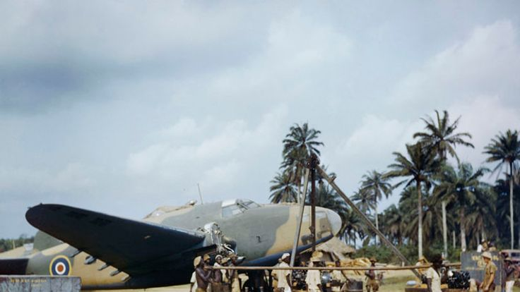 Local workers helping RAF fitters change the engine of a Lockheed Hudson at Yundum in the Gambia, April 1943