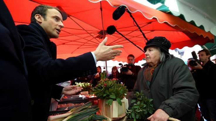 Emmanuel Macron speaks with a stallholder in a market in Poitiers, central France