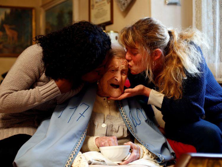 Emma Morano is kissed by her caretakers Malgorzat Ceglinska and Yamilec Vergara during the 117th birthday