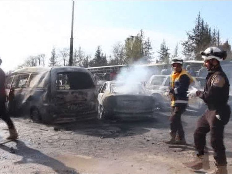 Rescuers search through burnt our cars and buses
