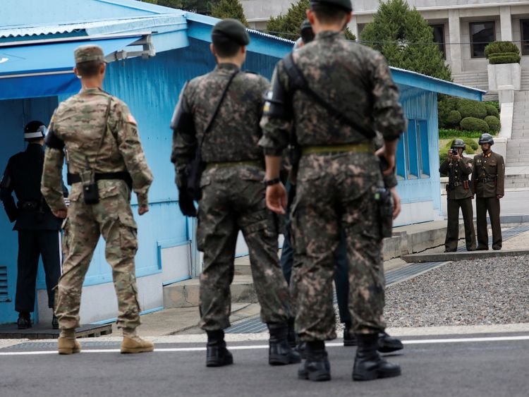 A North Korean soldier takes photographs as Mike Pence arrives in Panmunjom