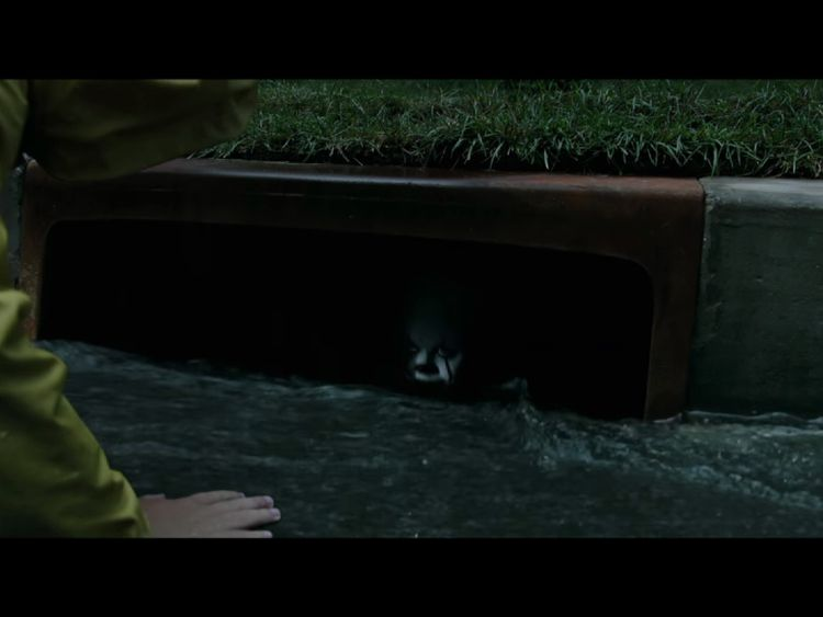 Pennywise is initially seen peeping out from a drain. Pic: Warner Bros.
