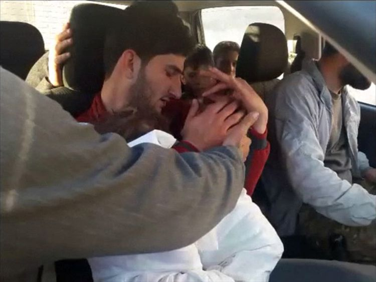 Abdel Hameed al-Youssef cradles his dead twins after the suspected chemical attack