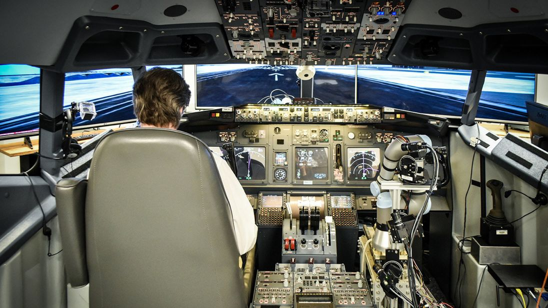 An IT specialist at the John A. Volpe National Transportation Systems Center flies a Boeing 737-800NG simulator with Aurora's ALIAS technology demonstration system as his co-pilot.