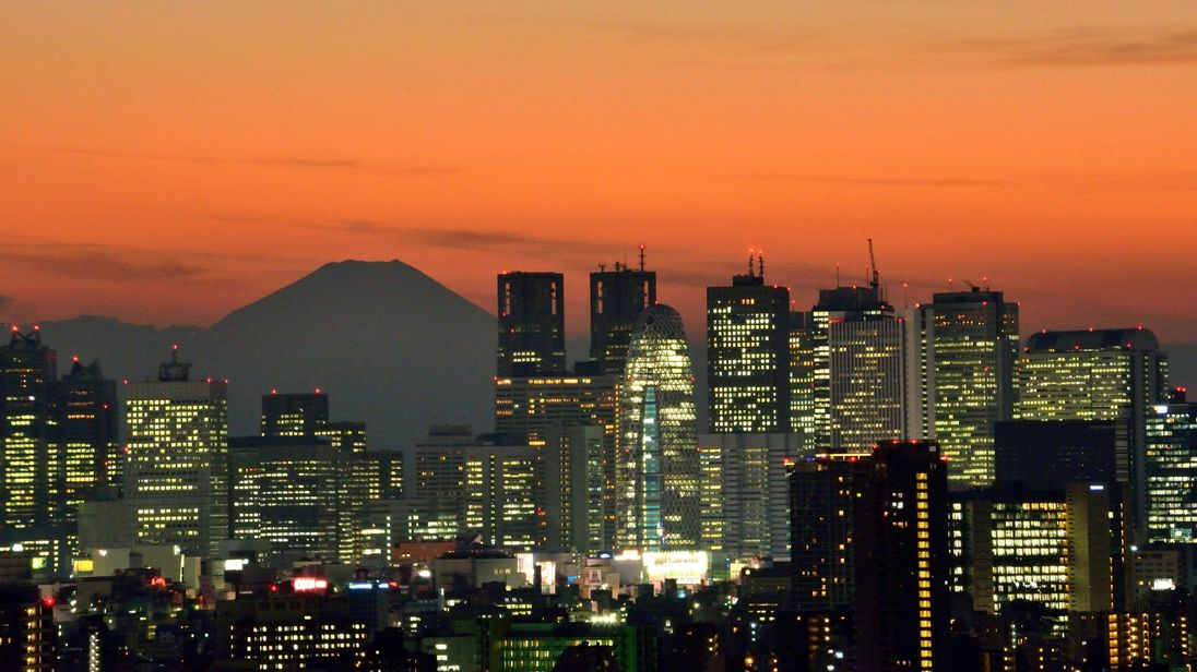 Japan's highest mountain Mount Fuji (top L) is seen behind the skyline of the Shinjuku area of Tokyo at sunset on November 27, 2014.