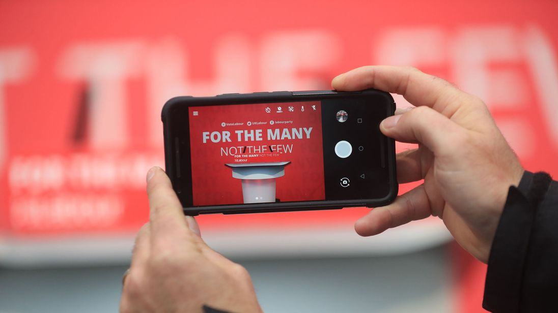 An audience member points a phone ahead of Jeremy Corbyn's launch of the Labour manifesto