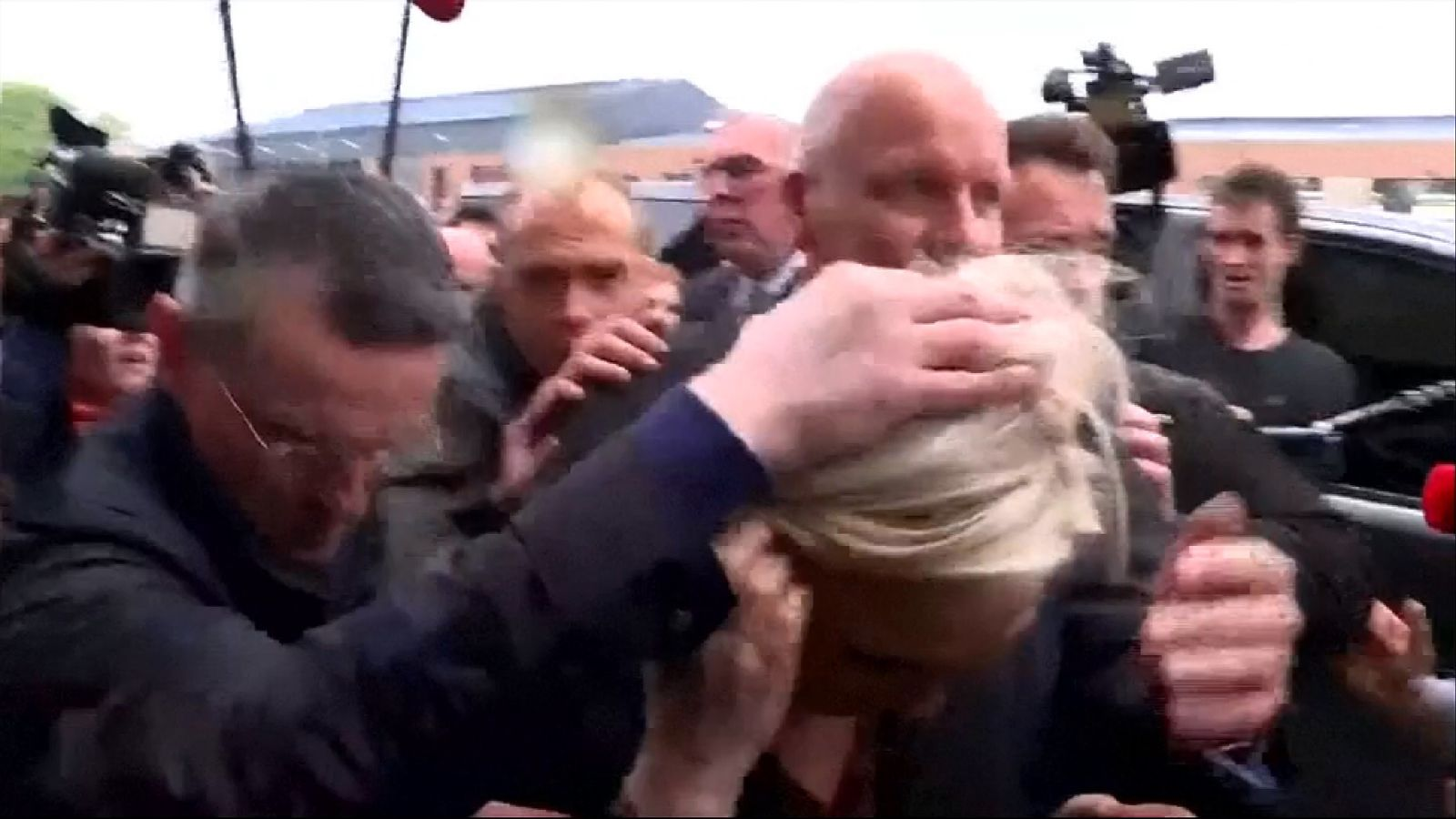 Security usher Marine Le Pen away after a protester throws an egg.