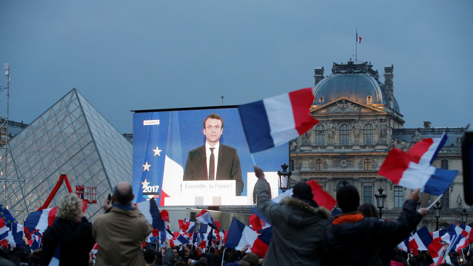 Emmanuel Macron is seen on a giant screen after the results were announced