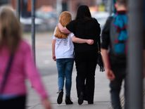 A woman and a girl wearing a t-shirt of US singer Ariana Grande leave a hotel near the Manchester Arena