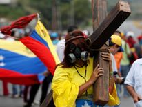 An opposition supporter carrying a cross attends a rally against Venezuela's President Nicolas Maduro in Caracas