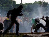 Opposition supporters clash with riot police while rallying against Venezuelan President Nicolas Maduro in Caracas