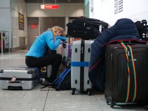 A traveller sleeps next to luggage at Heathrow Airport Terminal 5