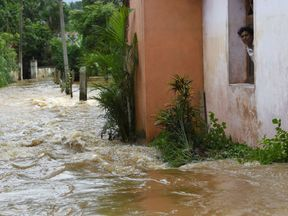 A resident in a suburb of the capital, Colombo, looks out at the flood waters