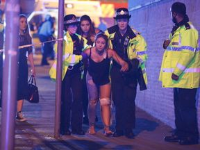 An injured concert goer is helped away from the Manchester Arena