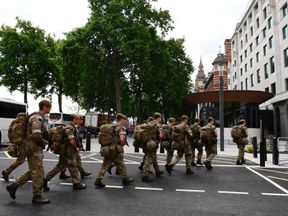 Soldiers arrive by bus and head toward a building next to New Scotland Yard
