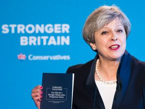 Theresa May brandishes the Conservative manifesto at its launch in Halifax