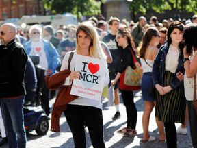 A woman waits to take part in a vigil for the victims of an attack on concert goers at Manchester Arena