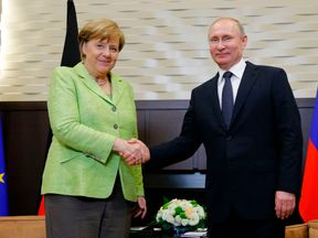 Russian President Vladimir Putin shakes hands with German Chancellor Angela Merkel during their talks in Sochi