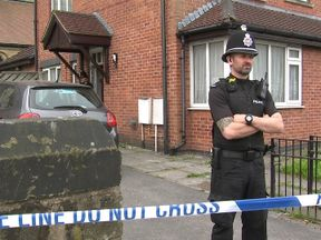 Police officers guard house raided as part of investigation into bomb attack