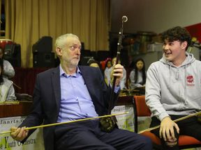 Jeremy Corbyn playing an Erhu - sometimes known as a Chinese violin - in Liverpool