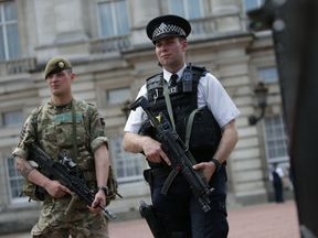 A solider and armed policeman guard Buckingham Palace