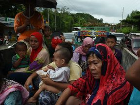 Evacuees from Marawi city are checked by police before entering Iligan city in the Philippines