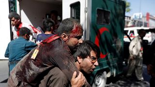 An injured man is carried to a hospital after the blast in Kabul