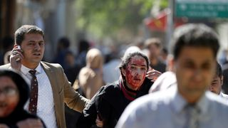 An injured woman is helped away from the blast site
