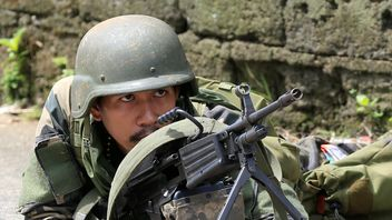A government soldier positions himself during an assault with insurgents