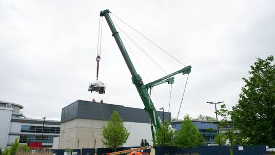 The proton beam therapy machine is hoisted into position